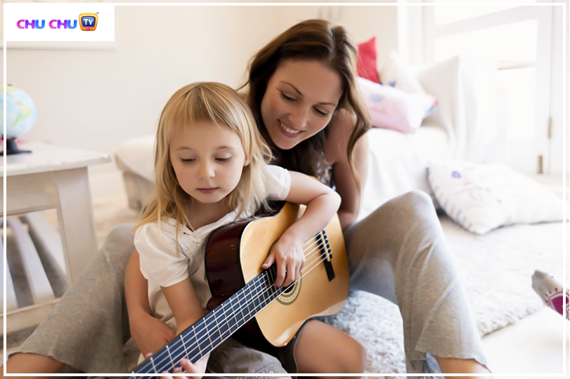 mother teaching guitar to her daughter